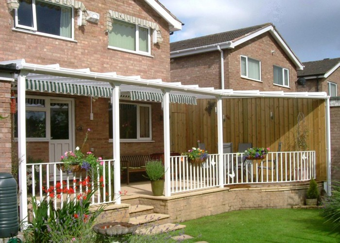 White Patio canopy shaped to follow the line of some decking